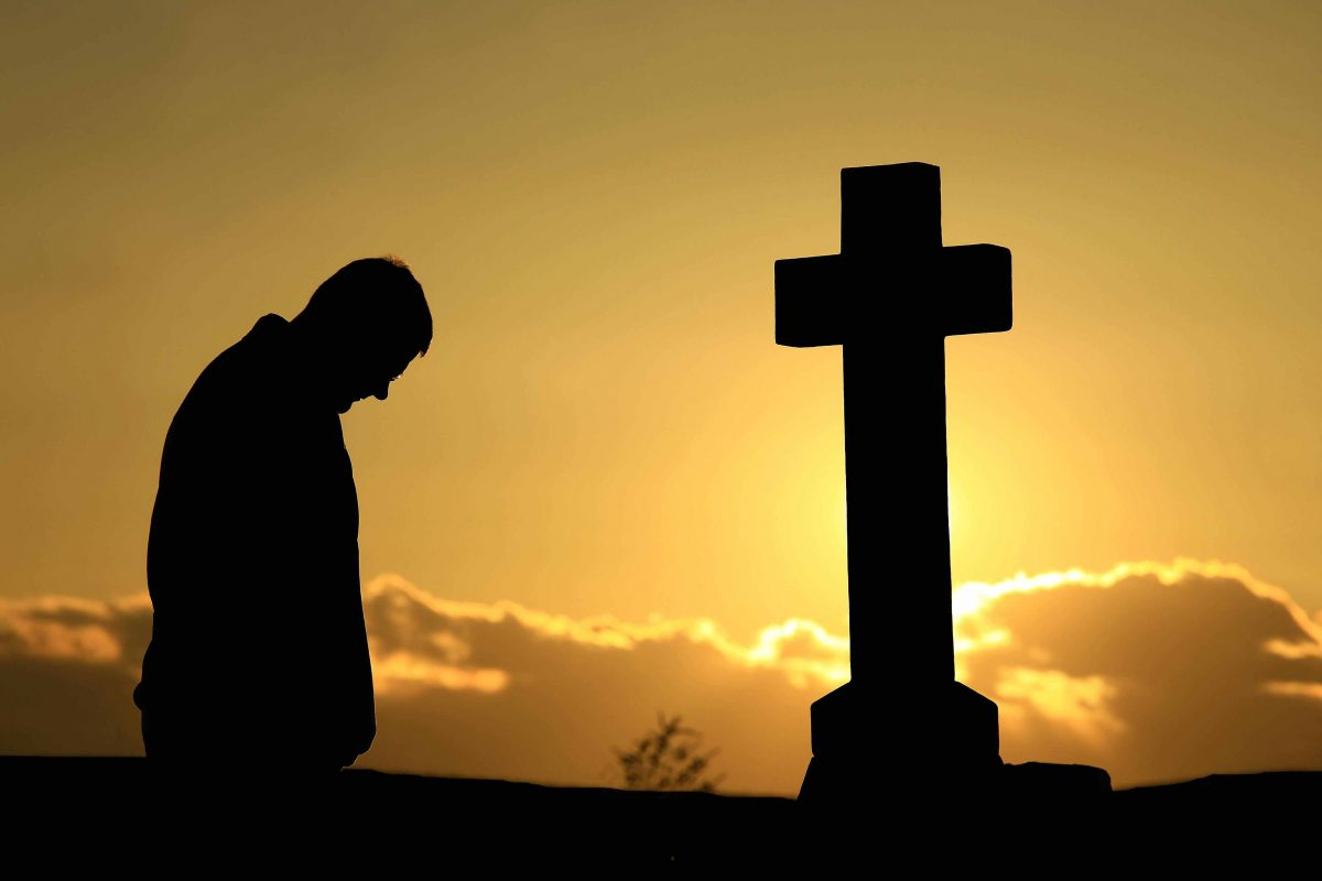 November is the month of the Holy Souls. Image shows a man praying beside a grave at sunset.