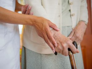 Carer helping elderly woman to walk